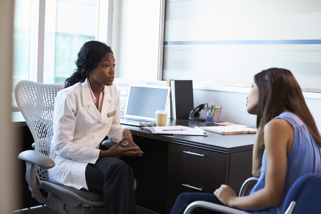 Woman in female doctor's office in discussion